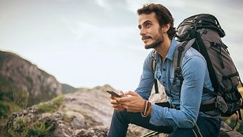 Junger Mann mit Rucksack tippt auf Smartphone