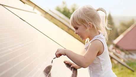 Kleines blondes Kind spielt an Photovoltaikanlage